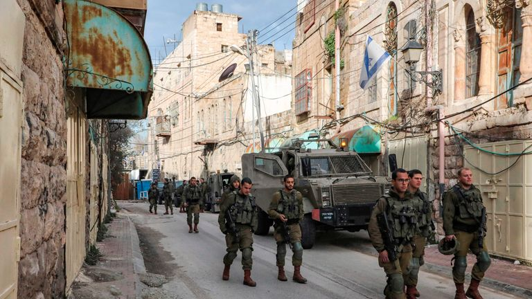 Israeli soldiers patrol past closed-down Palestinian shops along the Israeli-controlled Shuhada street in the flashpoint city of Hebron in the occupied West Bank on January 28, 2020. (Photo by HAZEM BADER / AFP) (Photo by HAZEM BADER/AFP via Getty Images)
