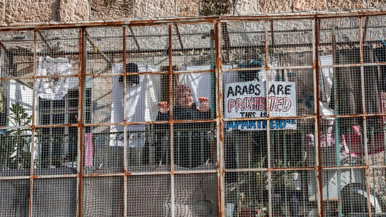 "A Palestinian woman stands in a veranda, covered with metal meshing, as she stands next to a protest sign reading in English ""Arabs are prohibited, this is Apartheid St."", from her house overlooking the Israeli-controlled Shuhada street (whose main entrance is blocked) in the flashpoint city of Hebron in the occupied West Bank on January 28, 2020. (Photo by HAZEM BADER / AFP) (Photo by HAZEM BADER/AFP via Getty Images)"