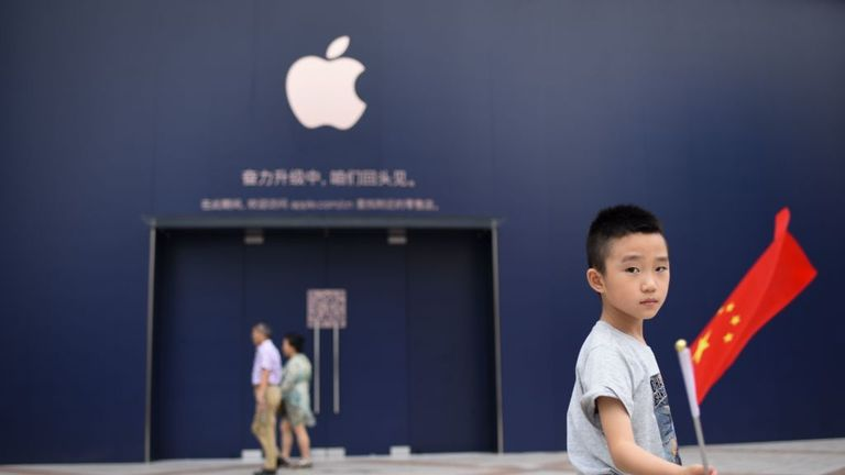 A boy holds a Chinese flag as he walks past an Apple Store undergoing renovation in Beijing on July 18, 2018. (Photo by WANG ZHAO / AFP) (Photo credit should read WANG ZHAO/AFP via Getty Images)