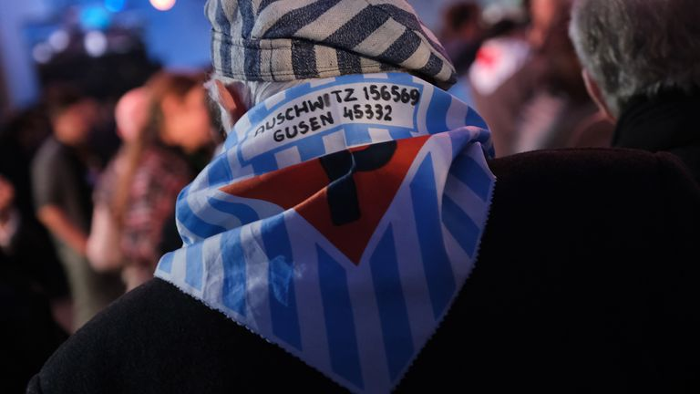 Some Polish survivors wore striped scarves that recalled the prison garb they wore at the time