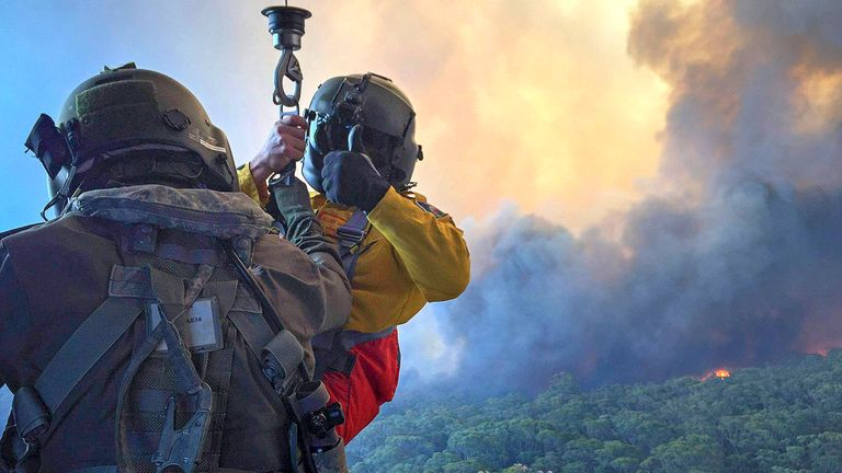 Rural Fire Service employee, Allen Madden prepares to be winched down in the Lithgow area by Petty Officer Aircrewman Jason Wickman from an 808 Squadron MRH90 Taipan Military Support Helicopter over the Grose Valley bushfire in the Blue Mountains National Park