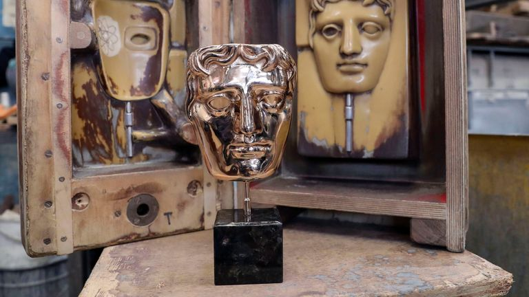 A finished mask sits in front of the moulds during the casting of the British Academy of Film and Television Awards (BAFTA) masks at a foundry in West Drayton, west London, ahead of the ceremony on February 2