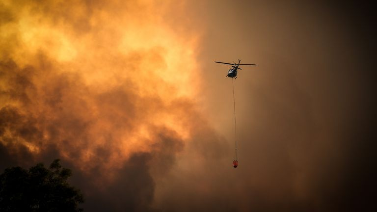 Helicopters dump water on bushfires as they approach homes located on the outskirts of the town of Bargo on December 21, 2019 in Sydney, Australia