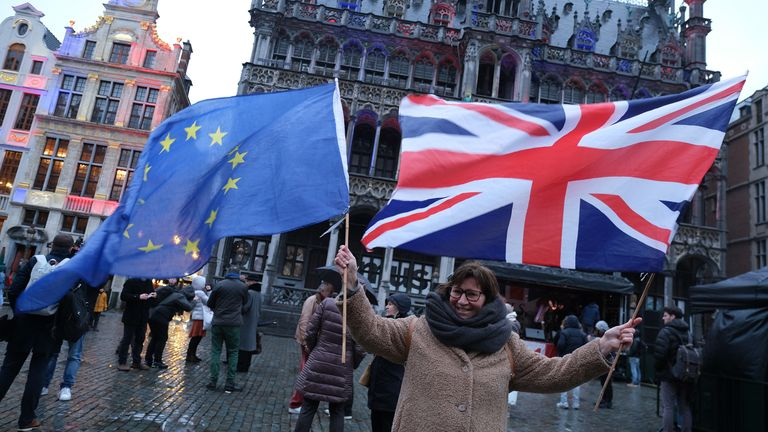 "BRUSSELS, BELGIUM - JANUARY 30: A British citizen living in Brussels arrives with EU and British flags on the Grand Place during a British-themed evening titled ""Brussels Calling"" and sponsored by the city the day after the European Parliament ratified the Brexit agreement on January 30, 2020 in Brussels, Belgium. The city of Brussels is hosting an event later in the day to honor the UK and its citizens. (Photo by Sean Gallup/Getty Images)"
