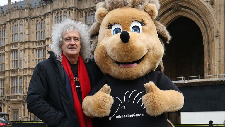 Brian May stands beside Grace the Hedgehog, mascot of the Save Me Trust, in College Green, opposite the Palace of Westminster in London