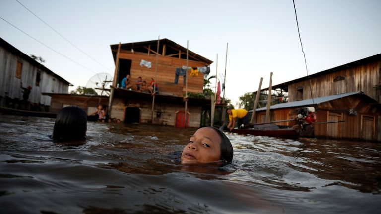 A child swims through a street flooded by the rising Rio Solimoes