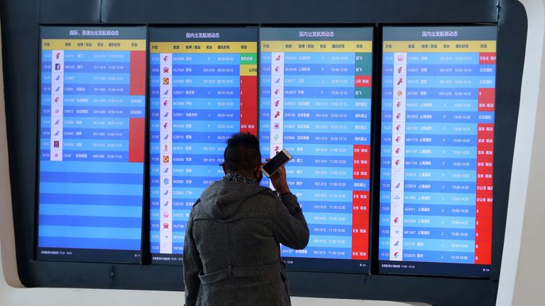A man stands in front of a screen showing that multiple departure flights have been cancelled at an airport in Wuhan, Hubei province