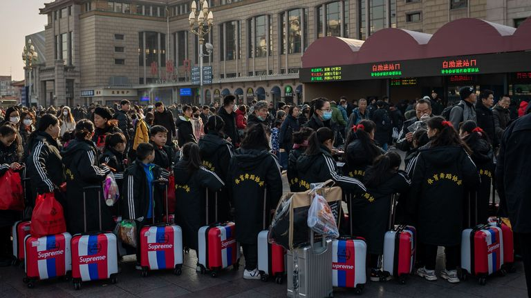 People queue up outside a Beijing rail station as they head home for the Lunar New Year