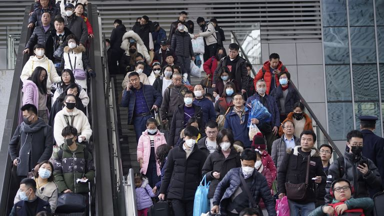 Passengers at Shanghai railway station wear facemasks as they travel home for the Lunar New Year