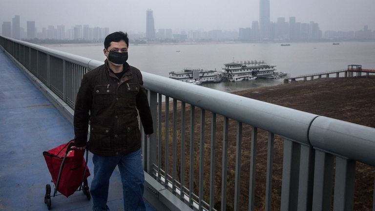WUHAN, CHINA - JANUARY 27:  A man wear mask while dragging a cart. in Yangtze River Bridge on January 27, 2020 in Wuhan, Hubei province, China. Public transport has been closed for the fourth day .  (Photo by Getty Images)
