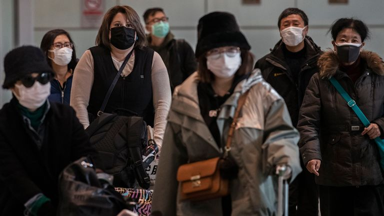 Passengers wear protective masks as they arrive at Beijing Capital Airport