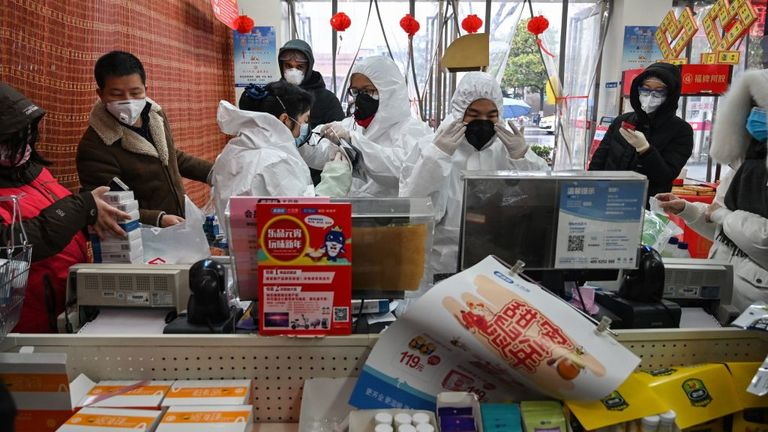 Pharmacy workers wearing protective clothes and masks serve customers in Wuhan