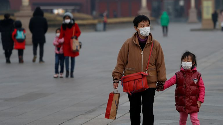People wearing face masks walk at the Tiananmen Gate, as the country is hit by an outbreak of the new coronavirus, in Beijing, China January 27, 2020. REUTERS/Carlos Garcia Rawlins