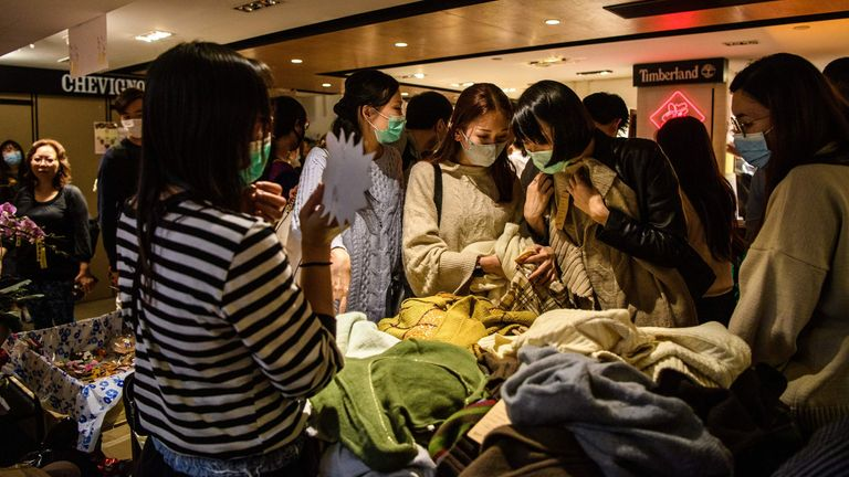 In this picture taken on January 23, 2020, shoppers wearing protective face masks browse clothes at a stall set up as part of a pro-democracy themed Lunar New year market in a shopping mall in Hong Kong