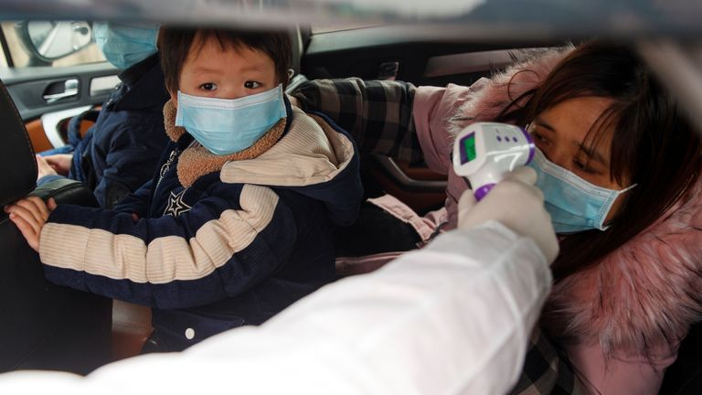 A medical worker in protective suit checks the body temperature of car passenger at a checkpoint outside the city of Yueyang, Hunan Province, near the border to Hubei Province
