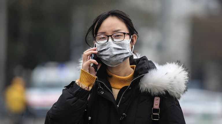 A woman wears a mask near the Huanan seafood market where the virus is thought to have originated