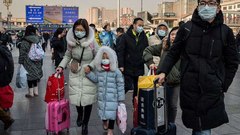 People wearing protective masks arrive at Beijing railway station to head home for the Lunar New Year on January 21, 2020