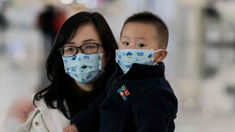 A woman and her child are seen wearing protective masks in the Chinese capital