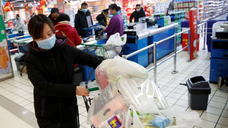 A woman wearing a face mask loads a shopping trolley in a supermarket in Changsha