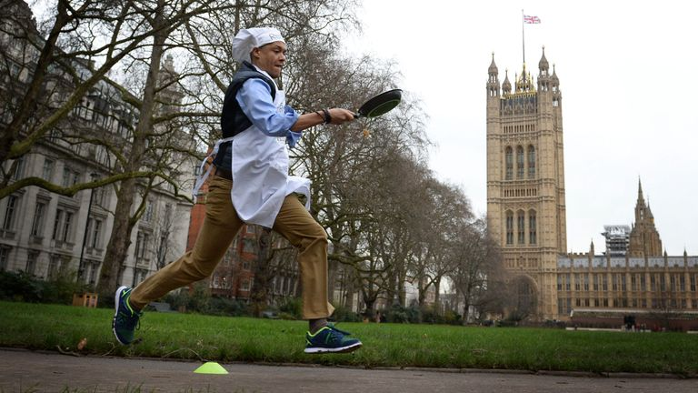 Norwich South MP Clive Lewis takes part the annual Rehab Parliamentary Pancake Race in which MPs, Lords and members of the media race each other on pancake day to raise money for the charity Rehab, in Victoria Tower Gardens, London