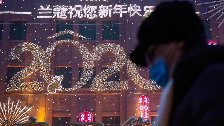 A woman walks in front of a New Year's sign in Wangfujing on January 26, 2020 in Beijing, China