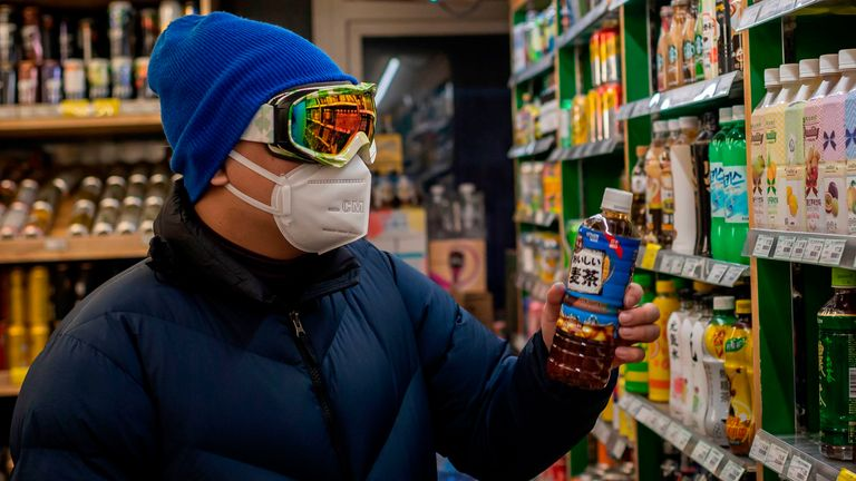 A man wearing a protective facemask, goggles and gloves at a supermarket in Beijing