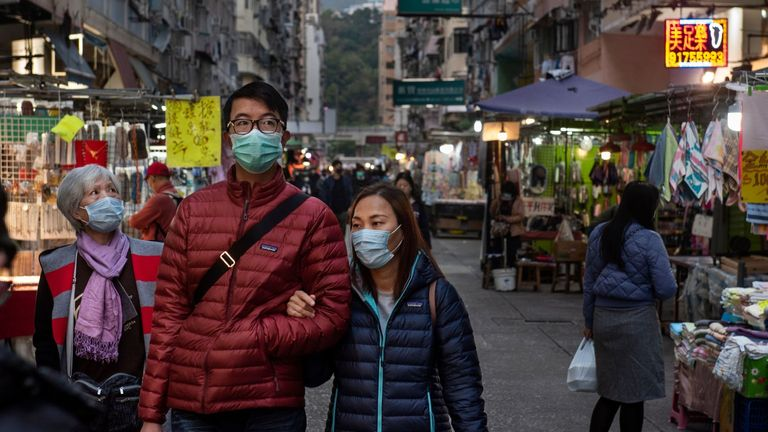 People wear face masks to prevent infections at a street market in Hong Kong