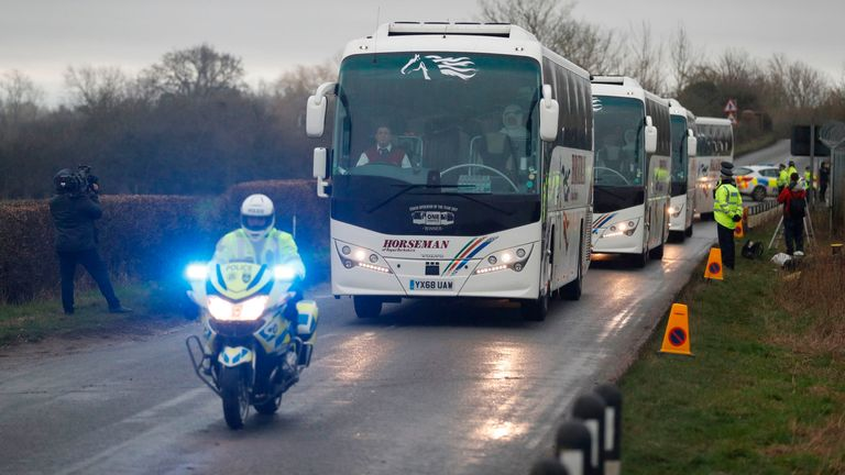 A convoy of coaches carrying British nationals evacuated from Wuhan in China amid the novel coronavirus outbreak and medical personnel in a protective suit drive away from the Royal Air Force station RAF Brize Norton in Carterton, west of London, on January 31, 2020 headed to accomodation at an NHS facility on the Wirral in northwest England. - A charter plane carrying evacuees from the Chinese city at the centre of the deadly novel coronavirus outbreak arrived at Royal Air Force base Brize Nort