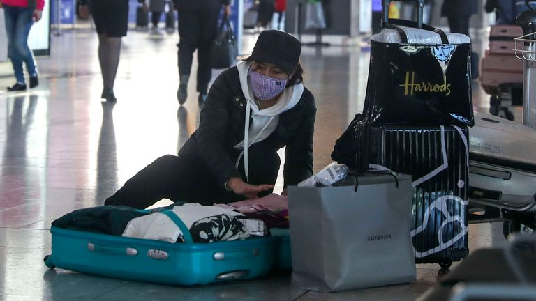 A woman wearing a face mask packs her suitcase in the departures area of Terminal 5 at Heathrow Airport