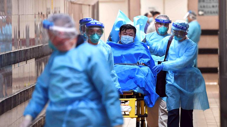 Medical staff transfer a patient of a highly suspected case of a new coronavirus at the Queen Elizabeth Hospital in Hong Kong