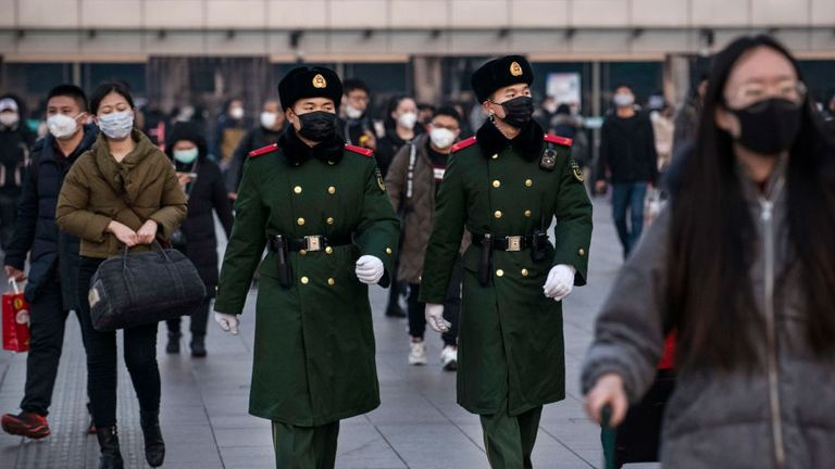 Chinese police officers wear protective masks as they patrol at Beijing Station