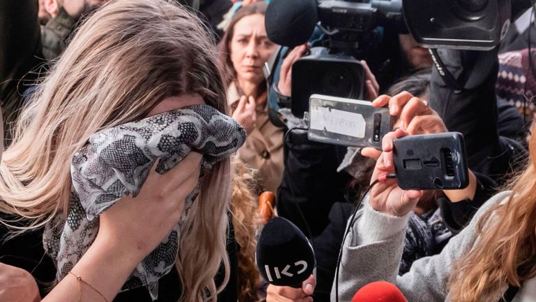 A British teenager, convicted of falsely accusing a group of Israelis of gang-rape, covers her face as she arrives at the Famagusta District Court in Paralimni