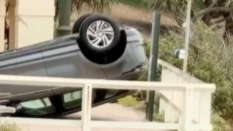 A car lands on its roof after crashing a barrier at Bondi Beach