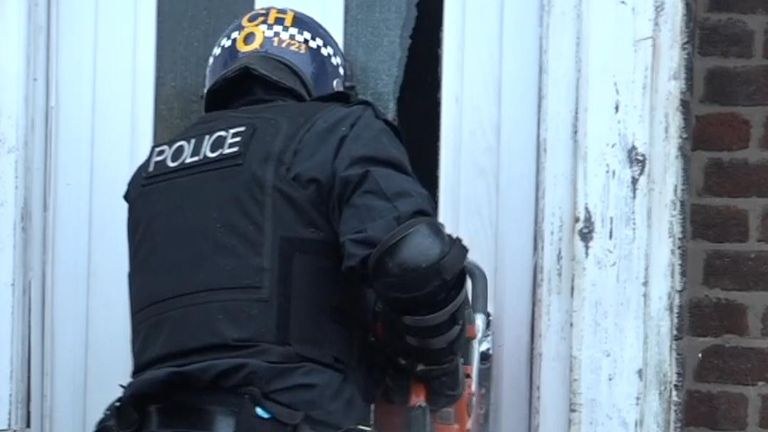 Police saw through a door during a drugs raid in Liverpool