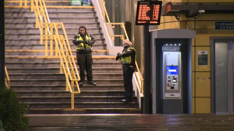 Police officers stand outside East Croydon railway station