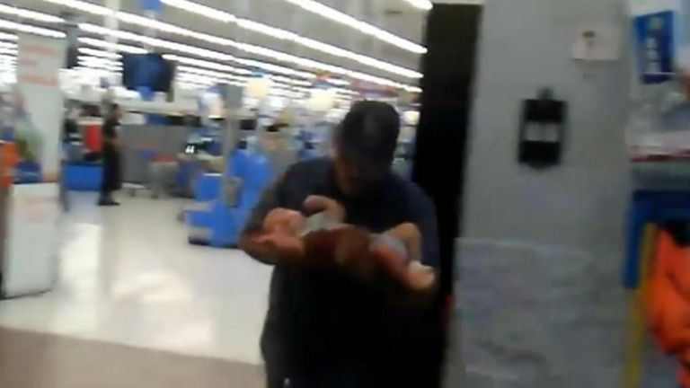 Lazaro Ponce carries baby Paul from the el Paso Walmart pic: Lem Arrendondo