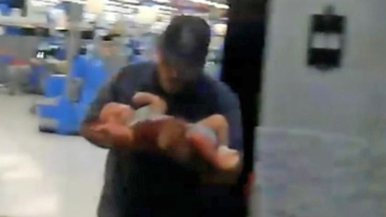 Lazaro Ponce carries baby Paul from the El Paso Walmart. Pic: Lem Arrendondo