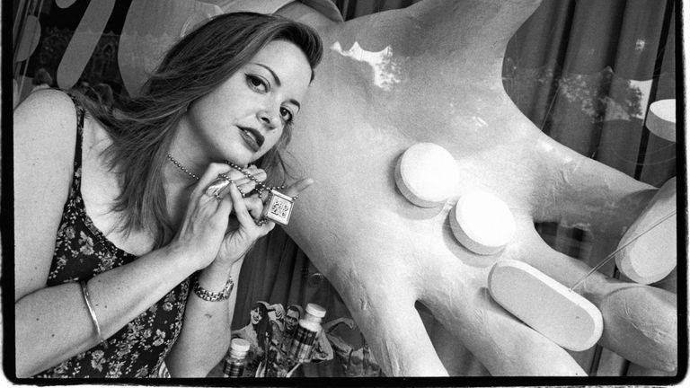 """Wurtzel holds up a locket with the word """"Prozac"""" on it and poses in front of a window display of a hand holding pills in New York in 1991"""