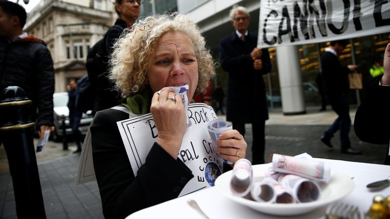 A protester eats fake money outside the BlackRock office during an Extinction Rebellion demonstration in London. Pic: REUTERS/Henry Nicholls