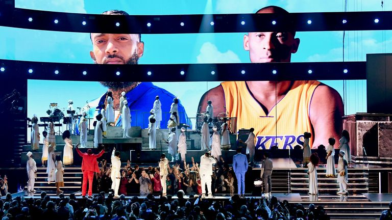 Images of the late Nipsey Hussle and Kobe Bryant are projected onto a screen while YG, John Legend, Kirk Franklin, DJ Khaled, Meek Mill, and Roddy Ricch perform onstage during the 62nd Annual GRAMMY Awards at STAPLES Center on January 26, 2020 in Los Angeles, California