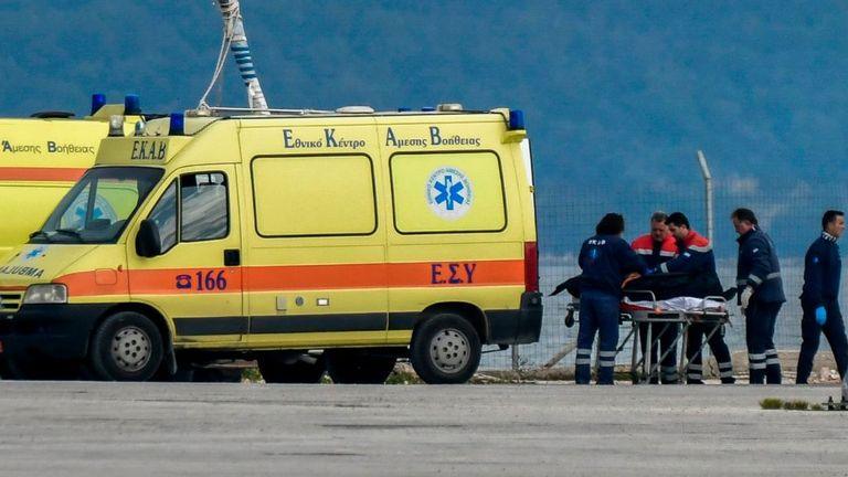 Medical staff transfer the body of a migrant into an ambulance at the port of Preveza