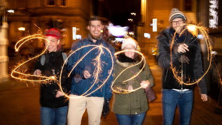 Four visitors from France have fun with some sparklers during Hogmanay