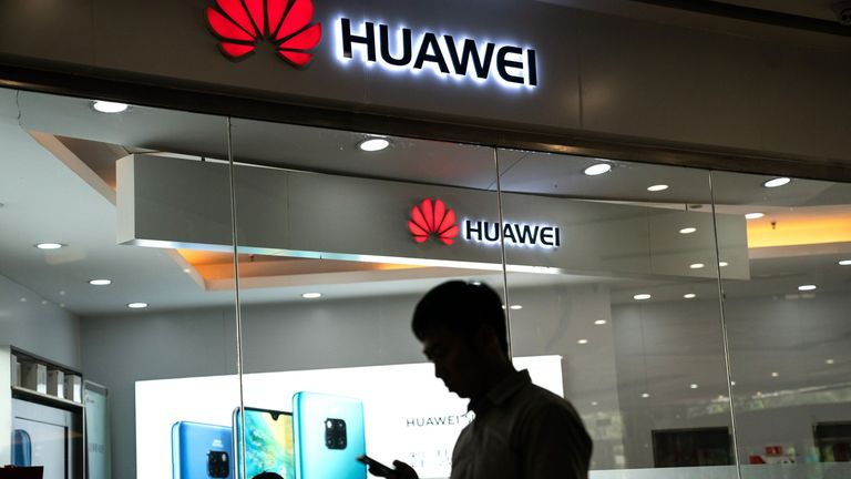 A man walks past a Huawei logo displayed at a retail store in Beijing on May 23, 2019