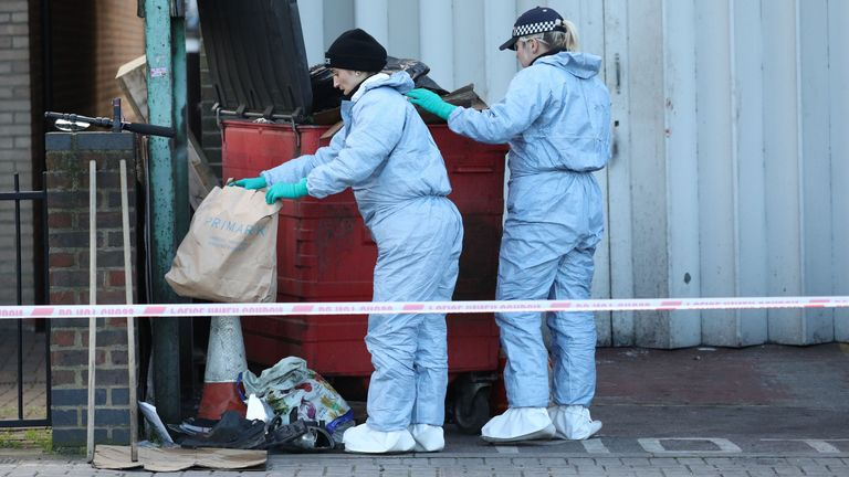 Scenes of crime officers (SOCO) search through a bin near the scene