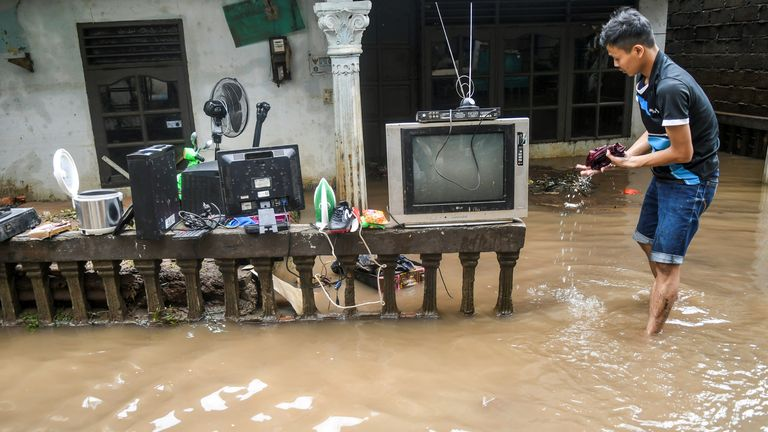 A man collects his belongings after floods hit Jakarta, Indonesia. Pic: Antara Foto/ Galih Pradipta/Reuters