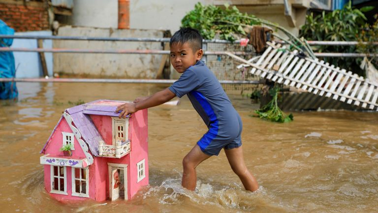 A boy pushes a toy house in floodwaters after heavy rains in Jakarta, Indonesia