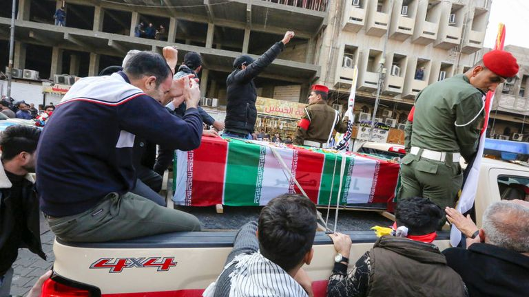 Iraqis mourn over a coffin during the funeral procession which drew thousands of supporters to the streets
