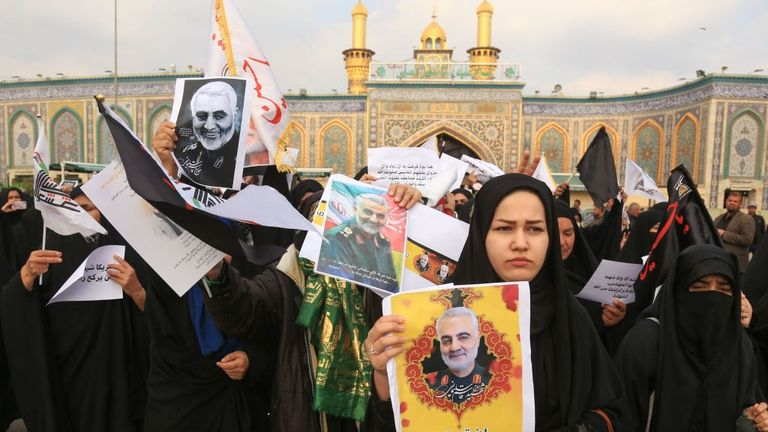 Mourners holding pictures of Gen Maj Soleimani wait for the funeral procession outside the Imam Abbas mosque in Karbala, central Iraq