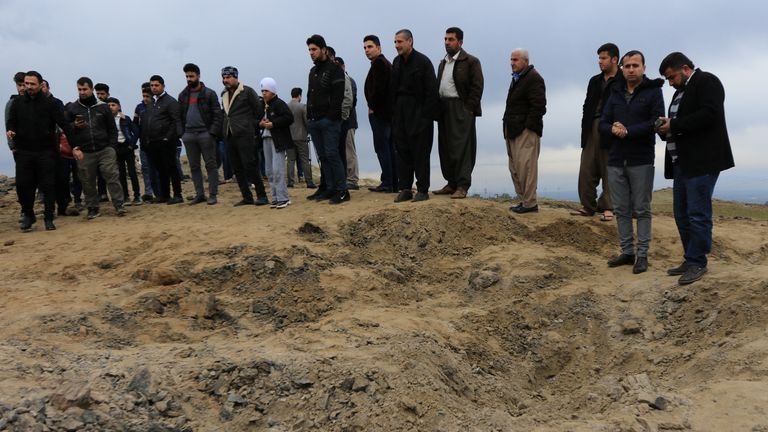 Men look over a crater caused by a missile fired by Iran at US-led coalition forces in Duhok, Iraq