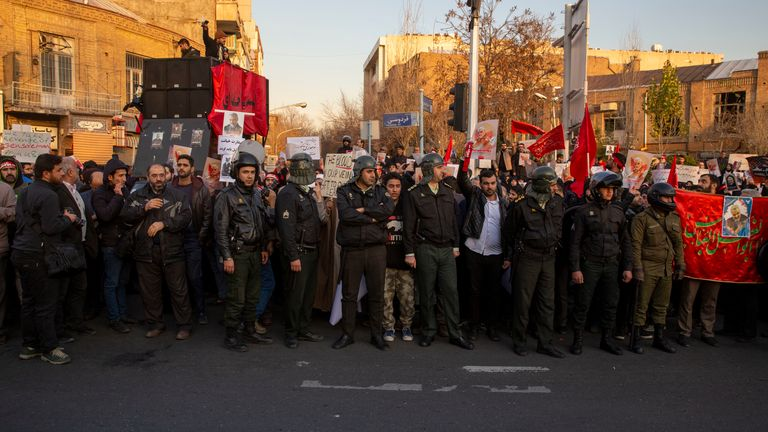 Protesters chant slogans while holding up posters of Gen. Qassem Soleimani during a demonstration in front of the British Embassy